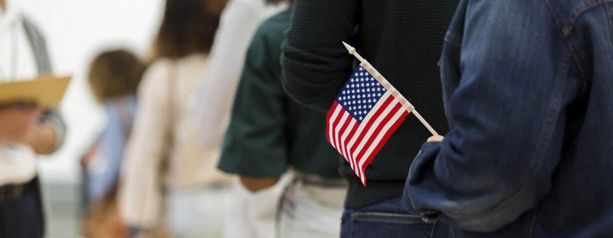 Citizen standing in line to vote carrying a small American flag